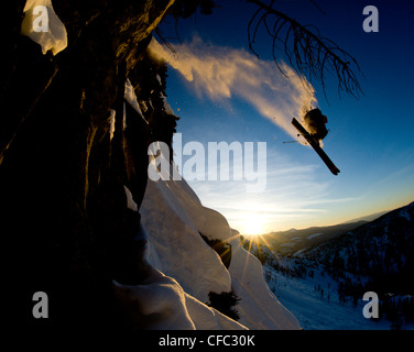 A young male skier takes huge air off a cliff in the backcountry near Whitewater Winter Resort, British Columbia, - Stock Photo