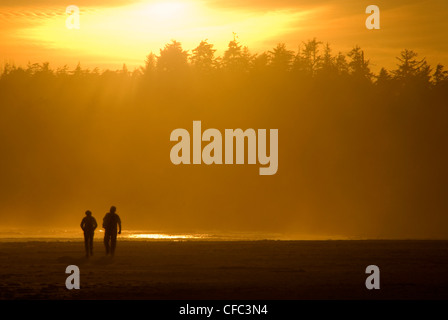 Tofino silhouette of couple walking on Long Beach. - Stock Photo
