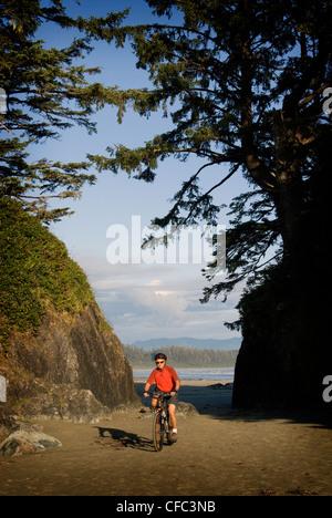Asian man bike riding on Tofino Beach riding towards the camera smiling. - Stock Photo