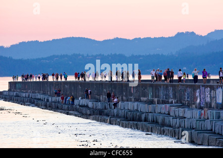 People stroll along Ogden Point waterbreak during - Stock Photo