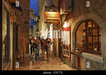 People on an alley of the old town in the evening, Budva, Montenegro, Europe - Stock Photo
