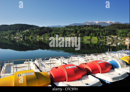 Multicolored pedal boats at lake Millstaetter See with snow covered mountains in the background, Seeboden, lake - Stock Photo