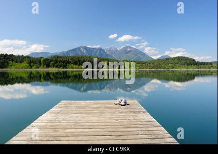 Sneakers standing on wooden landing stage in lake Turnersee, Karawanken range in background, lake Turnersee, Carinthia, - Stock Photo