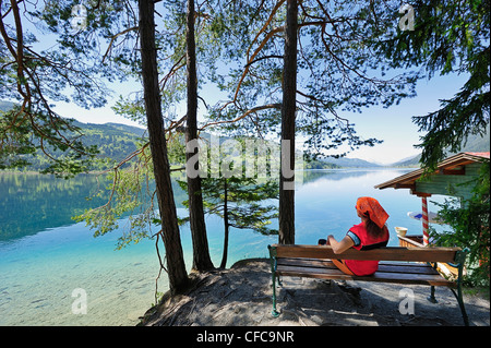 Woman sitting on wooden bench and enjoying view of lake Weissensee, lake Weissensee, Carinthia, Austria, Europe - Stock Photo