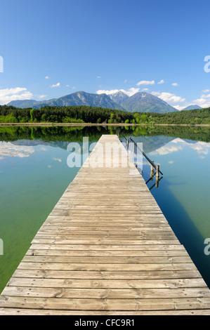 Wooden landing stage leading into lake Turnersee, Karawanken range in the background, lake Turnersee, Carinthia, - Stock Photo