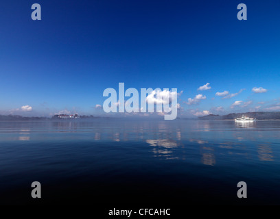 View across the reflecting lake towards Herreninsel, ferry boat, Lake Chiemsee, Chiemgau, Bavaria, Germany - Stock Photo