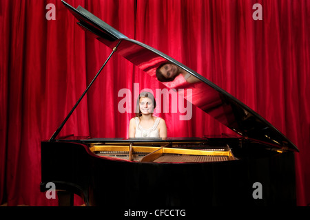 Young girl, smiling whilst playing on a grand piano in front of the red curtains on stage - Stock Photo