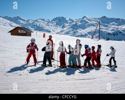 Children in ski school lined up on the piste in Courchevel Three Valleys France - Stock Photo