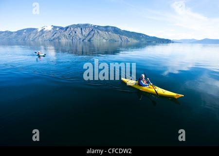 An happy adventurous retired couple kayaking on a huge calm lake in Idaho. - Stock Photo