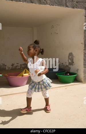 Boa Vista Cape Verde Young local girl dancing whilst holding a cake in her hand - Stock Photo