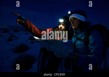 Two women discuss what route to take while hiking in the Sierra Foothills outside of Lake Tahoe, California. - Stock Photo