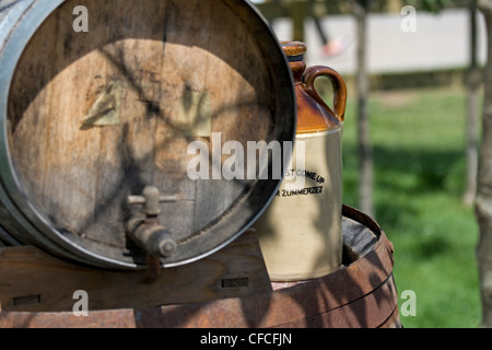 Cider flagon next to barrel - Stock Photo