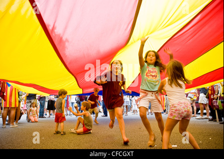 Children play and enjoy under a big catalan flag during the Catalan National Day in Barcelona. - Stock Photo