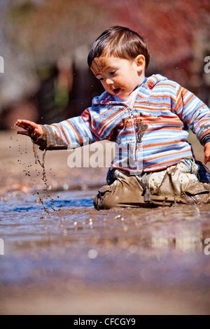 a two year old boy, plays in a mud puddle. - Stock Photo