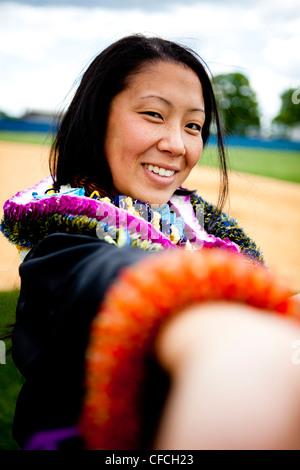 A graduate shows a Hawaiian Lei (lay) on her wrist. - Stock Photo