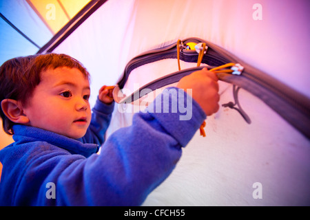 a little boy opens and closes the zippered tent door while he stands on a blue sleeping bag. The tent is orange - Stock Photo