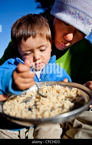 a boy sits on his mothers lap while they eat noodles in the backcountry. They are camped at Squaw Pass. - Stock Photo