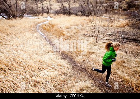 a young woman runs a down trail through dead grass just north of Dixon Reservoir, on a cold day in a green down - Stock Photo