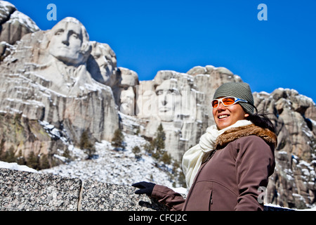 a thirty year old, Japanese-American woman stands in front of Mt Rushmore National Memorial. - Stock Photo