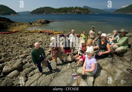 Paddlers Misty Isle's kayak business pose group - Stock Photo