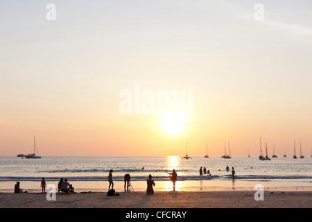 People on Nai Harn beach at sunset, Phuket, Thailand, Asia - Stock Photo
