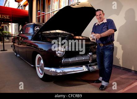 Custom car owner checks oil of 1949 Mercury Sedan/Coupe Custom - Stock Photo