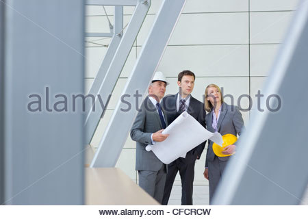 Architects and engineer holding blueprints in office - Stock Photo