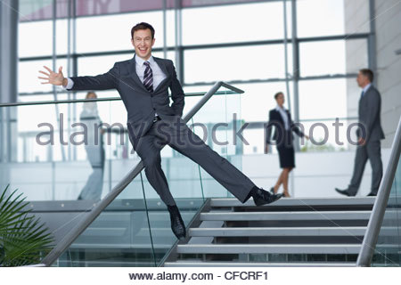 Portrait of enthusiastic businessman in suit sliding down railing in lobby - Stock Photo
