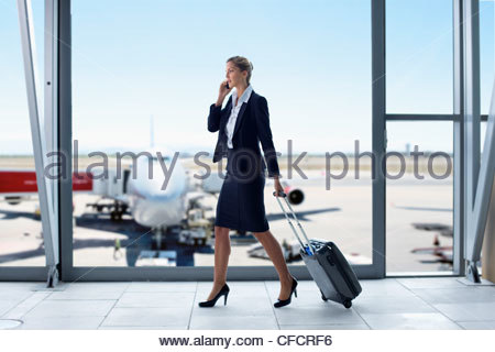 Businesswoman in suit pulling suitcase and talking on cell phone at airport window - Stock Photo