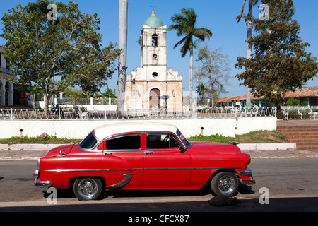 Classic red American car parked by the old square in Vinales village, Pinar del Rio, Cuba, West Indies, Central - Stock Photo