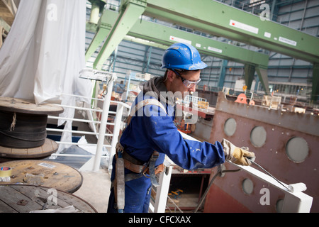 Worker painting railing, cruiser under construction in dry dock, Meyer Werft, Papenburg, Lower Saxony, Germany - Stock Photo