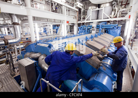Assemblers in engine room, cruiser under construction in dry dock, Meyer Werft, Papenburg, Lower Saxony, Germany - Stock Photo