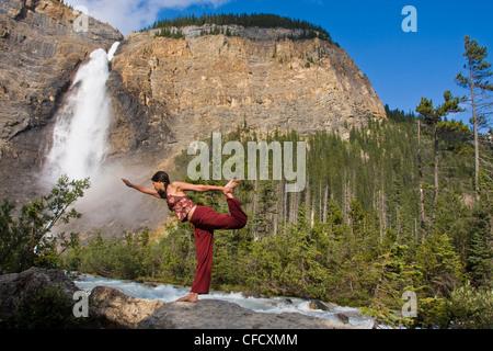 Young woman practicing yoga beneath Takakkaw Falls in Yoho National Park, Field, British Columbia, Canada - Stock Photo