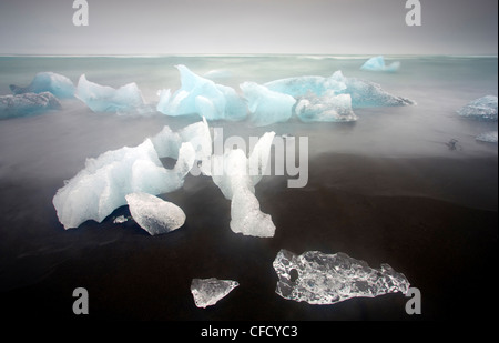 Icebergs from the Jokulsarlon glacial lagoon washed up on a nearby volcanic sand beach from the North Atlantic Ocean, - Stock Photo