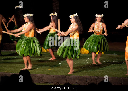 Hula dancers with Pūʻili (split bamboo sticks), Old Lahaina Luau, Maui, Hawaii, United States of America - Stock Photo