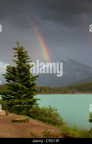 Canoes and rainbow over Lower Waterfowl Lake, Banff National Park, Alberta, Canada - Stock Photo