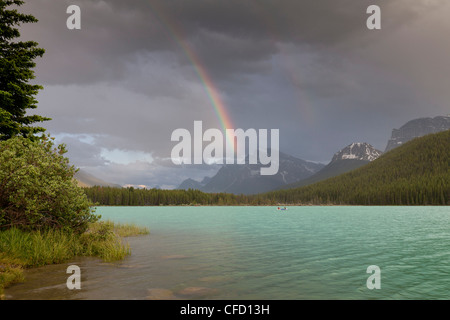 Boats and a canoe with rainbow over Lower Waterfowl Lake, Banff National Park, Alberta, Canada - Stock Photo