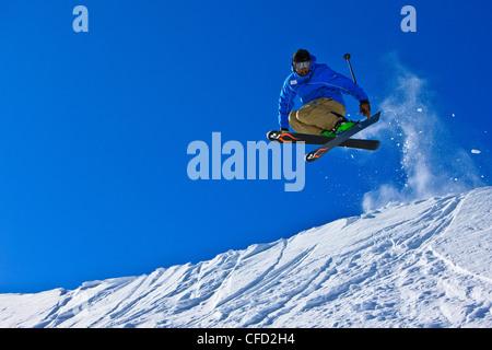 Skier jumping over a ridge on the upper slopes of Whistler Mountain, Whistler Blackcomb, Whistler, British Columbia, - Stock Photo