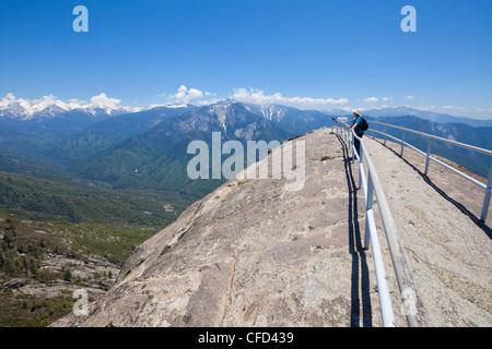 Hiker on top of Moro Rock, looking towards Kings Canyon, Sequoia National Park, California, USA - Stock Photo