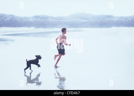 Boy running on beach with dog, high key, British Columbia, Canada. - Stock Photo