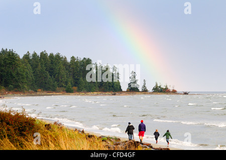 A family enjoys a walk along the beach in Parksville, British Columbia, Canada. - Stock Photo