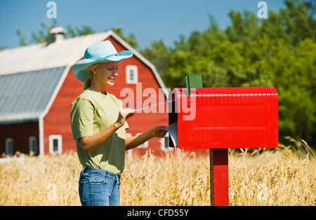 A girl checks a rural mailbox in front of a farmyard and spring wheat field, Grande Pointe, Manitoba, Canada - Stock Photo