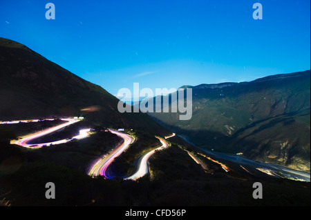 Moonlit valley and car light trails on a winding road in Chicamocha National Park, Colombia, South America - Stock Photo