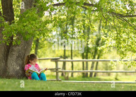 Younge girl reading a book under a tree in Northern Alberta, Canada. - Stock Photo