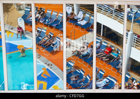 Pool area reflected on large panes of glass aboard Royal Caribbean's Allure of the Seas cruise ship. - Stock Photo