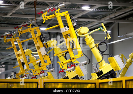 Yellow robots on a production line of cars manufacturing - Stock Photo
