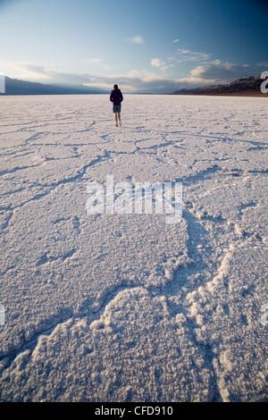 Woman walking on salt flats, Badwater Basin, Death Valley National Park, California, USA - Stock Photo