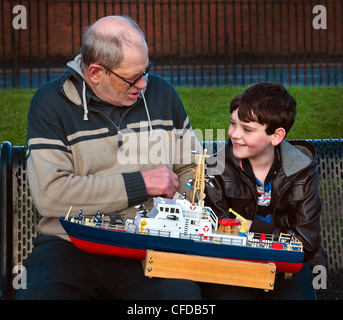 Young boy and old man discussing model boats in a park, Elderpark, Scotland Govan Glasgow - Stock Photo