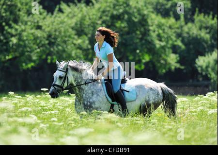 Woman riding a horse through a meadow, Inn Valley, Upper Bavaria, Bavaria, Germany - Stock Photo