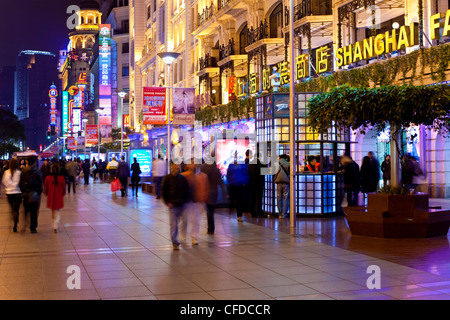 Pedestrians at night walking past stores on Nanjing Road, Shanghai, China, Asia - Stock Photo